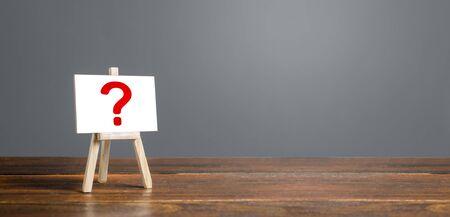 Staffelei mit Fragezeichen. Fragen stellen, nach der Wahrheit suchen. Neugier, lernen und verbessern. Geheimnis, Ermittlungsforschung. Umfrage Umfrage. Ankündigung der bevorstehenden Veranstaltung, Überraschung. Unbekannt Standard-Bild