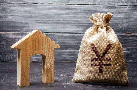 Yen yuan symbol money bag and house. Real estate purchase and investment. Affordable cheap loan, mortgage. Taxes, rental income. rent or buy. Home budget. Maintenance of a residential building. Stockfoto