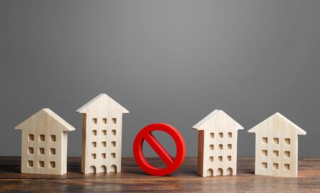 A red prohibition sign no stands among residential buildings. Restrictions ban on construction. Inaccessible expensive housing. Restriction building compaction. Underdeveloped infrastructure utilities