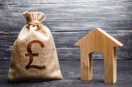 Pound sterling GBP symbol money bag and house. Real estate purchase and investment. Affordable loan, mortgage. Taxes, rental income. rent or buy. Home budget. Maintenance of a residential building. Archivio Fotografico