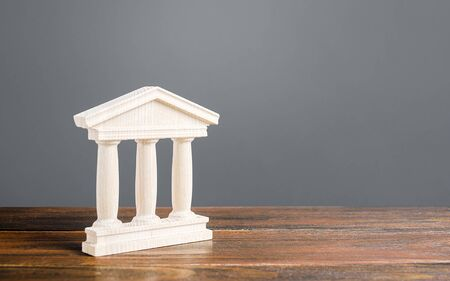 White building figurine with pillars in antique style. Concept of city administration, bank, university, court or library. Architectural monument in old town part . Banking, education, government. Stock fotó