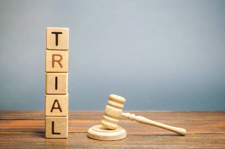 Wooden blocks with the word Trial and hammer of a judge. Settlement of disputes and consideration of criminal cases. Court. Gavel