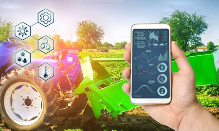 Farmer holds smartphone with infographic on tractor background with potato digger. Farming and smart agriculture. Agricultural machinery, data analyzing on plants status. Harvesting. Stock Photo