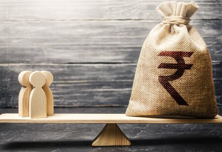 Indian rupee INR symbol on money bag and people on scales. concept attracting investment, business cooperation, crowdfunding and startup. Staff salary specialist services cost. Solvency, taxpayers Stock fotó