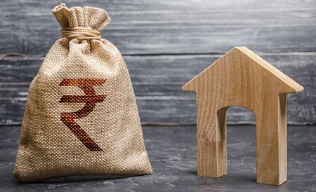 Indian rupee INR symbol money bag and house. Real estate purchase and investment. Affordable loan, mortgage. Taxes, rental income. rent or buy. Home budget. Maintenance of a residential building. Foto de archivo