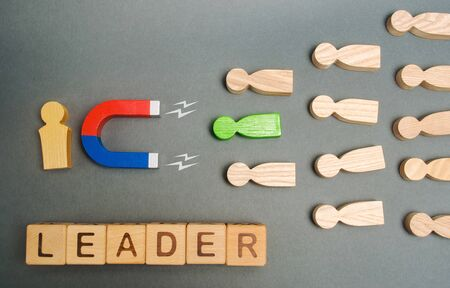 Magnet, crowd of workers and the word Leader on wooden blocks. Concept of choosing a new leader from the team. Leadership. Talented successful employee. Focus on the magnet