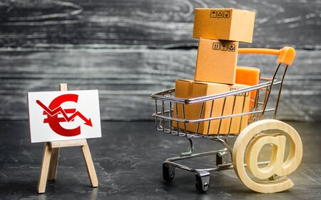 Shopping cart loaded with boxes, email symbol and euro red down arrow. Reduced online sales over Internet. Fall purchasing power. Price reduction. High competition. Low profits return on investment 免版税图像