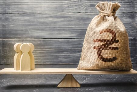 Ukrainian hryvnia UAH symbol on money bag and people on scales. concept attracting investment, business cooperation, crowdfunding startup. Staff salary specialist services cost. Solvency, taxpayers