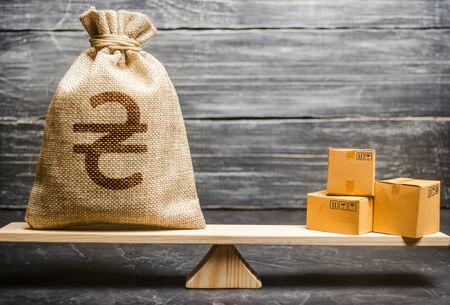 Hryvnia ucraniano UAH símbolo bolsa de dinero y un montón de cajas en escalas. Saldo de intercambio comercial. Importación y exportación, procesos económicos. Benefíciese de los productos manufacturados. Fabricación, distribución minorista