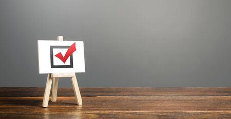 Easel with red voting tick. Checkbox. Democratic elections, referendum. Right to choose, change of power. Checklist verification, self-discipline. Necessary quality criteria, skills, approval symbol Foto de archivo - 135479087