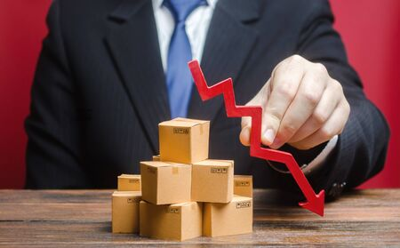 Businessman is holding a red arrow down above boxes stack pile. Business industrial production drop. Decrease freight transportation, volumes of delivery of products. Overproduction, scarcity of goods
