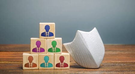 Wooden blocks with the image of a team of workers and a shield. Working staff insurance concept. Employee protection. Security and safety.