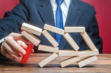 A businessman removes an important component causes collapse of entire complex system. Making wrong decisions, ruining business. Inexperience, unprofessional leader. Failure. Incompetent businessman.