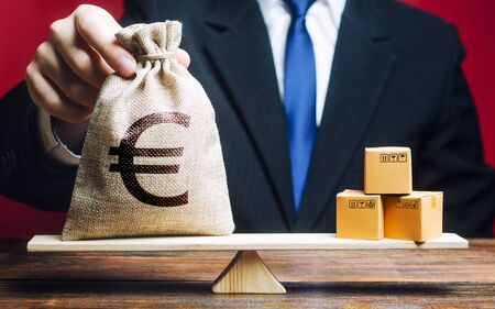 European euro EUR symbol money bag and a bunch of boxes on scales. Trade exchange balance. Import and export, economic processes. Profit from manufactured goods. Manufacturing, retail distribution