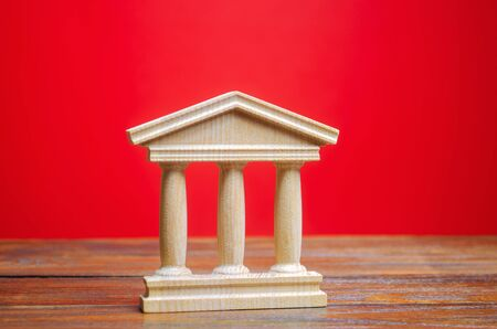 Government or court building on a red background. Building figurine with pillars in antique style. Concept of city administration, bank, university or library. Architectural monument