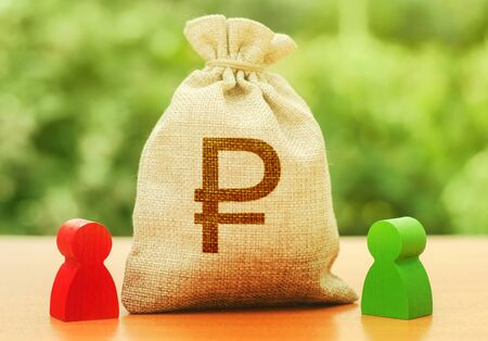Russian ruble money bag and two people figures. Business Investment and lending, leasing. Dispute solution between two businessmen. Division of property. Business relationship. Trade agreement deal Stock fotó