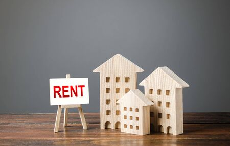 Three figures of houses and an easel with the word rent. Realtor services, search for optimal options. The concept of temporary rental housing and real estate. The choice between renting and buying. Stock fotó