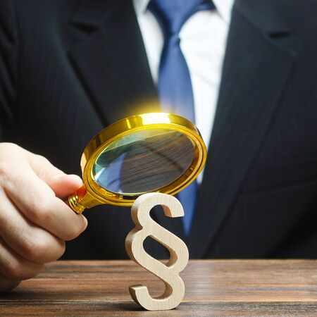 A man examines a paragraph figure with a magnifying glass. Judicial practice. Legitimacy. Studying laws and legislation, norms, rules. Legal service, lawyer services. Protection of rights, interests.