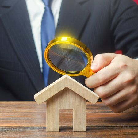A man is studying a house through a magnifying glass. Fair value of real estate. Property valuation. Legal deal. Standards and quality of construction. Legality and transparency of purchase agreement.