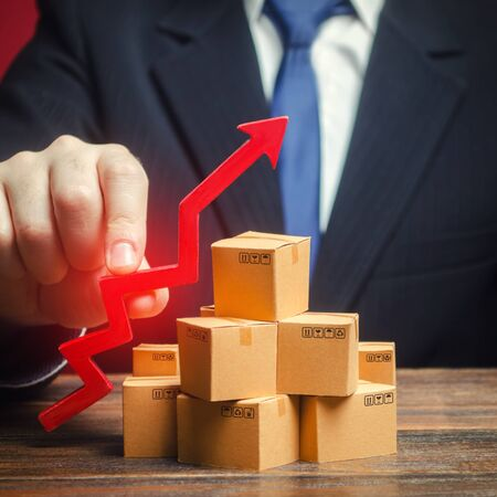 Businessman holding a red arrow up over boxes. Strategy marketing. Supply Demand. Increase sales rate, industrial goods production volumes growth , expanding export opportunities, finding new markets.
