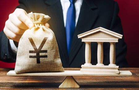 A man puts a Yen yuan money bag on scales opposite to building of government, bank, university. Budget and funding for normal functioning. Deposits and loans. Lobbying interests. Payment of taxes.