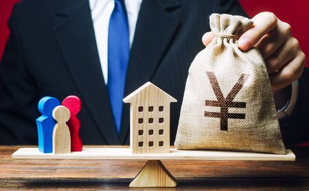 Man puts Yen yuan money bag and house on scales with a family. Mortgage, debt burden. Assistance with housing and financing for young families to stimulate childbirth demographic population growth.