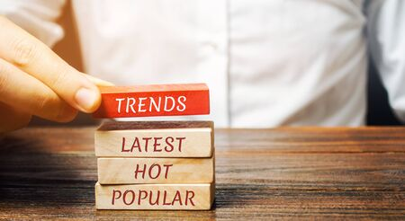 Businessman puts wooden blocks with the words Trends, latest, hot, popular. Popular and relevant topics. New ideological trends. Recent and latest trend. Evaluation methods.