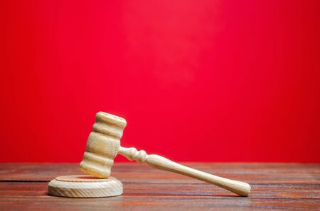 Judges hammer on a red background. The judicial system. Norms, rules and laws. Conflict resolution in court. Court case, settling disputes. Protection of their rights and freedoms, honor. Gavel Stock fotó