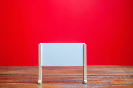 Stand or white board on a red background. Empty whiteboard. Minimalism. Business process concept, strategy planning at meetings and briefings. Education, presentation, message, creative platform