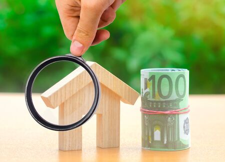 Euro banknotes stand near a wooden house. Concept of real estate market budget. Investment in construction. Saving money to buy a home or apartment. Affordable housing. Mortgage and debt. Taxes Stock fotó