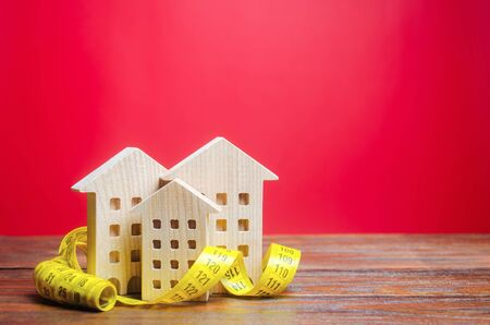Miniature wooden houses and measuring tape. Home appraisal and property valuation concept. Housing construction, repair and maintenance. Real estate appraiser