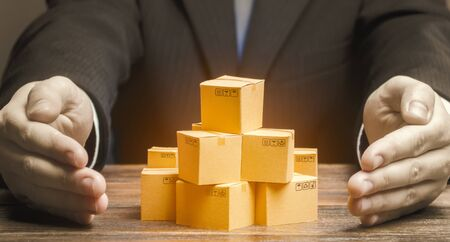 Businessman covers cardboard boxes with goods with his hands. Marketing and sales, distribution. Support for the manufacturer, attracting investment, promoting products to new markets. Brand creation Stock fotó