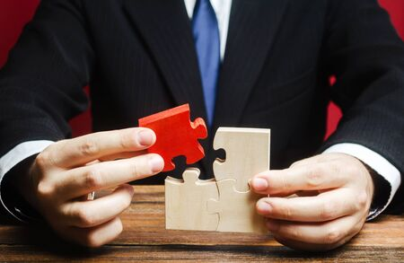 Businessman connects a red puzzle to the assembly. Business model planning and strategy, creating a new one. Innovation and development. Creating a new. Design, construction. System management