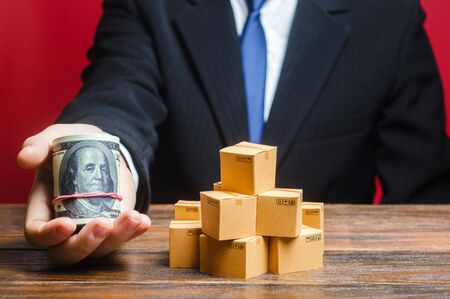 A businessman holds out a bundle of dollars near a pile of boxes. Trade and exchange goods, offers for cooperation. Profit, Superprofits. Investments financing in production, taxes, income revenues Stok Fotoğraf