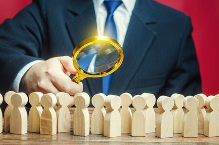 Man studying a crowd of people with a magnifying glass. Market and customers research. Hr search candidates for work, staff recruiting. Society, demographic. Citizens electorate. Analysis
