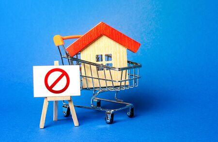 House in a shopping cart and an easel with a red prohibition sign NO. Inaccessibility, lack of housing, deficit. Seizure, freezing of assets by a bank, court. Illegal buildings, demolition elimination
