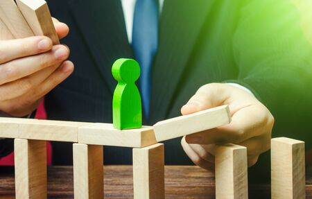 A businessman builds a path way for a green figure. Make a path to success, support and financial assistance. Build a business and company. Career growth and professional development. Education.