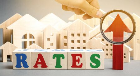 Wooden blocks with the word rates, up arrow and miniature houses. The concept of high interest rates on mortgages. Real estate. Credit. Loan Stok Fotoğraf