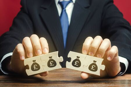 Businessman separates the wooden puzzle with a picture of money. The concept of financial management and distribution of funds. Saving and investing. Property division. Legal services. Stok Fotoğraf