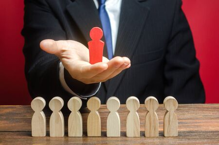 A man holds a leader figure over a team of workers. The best employee. Leadership and promotion. Human Resource Management and Recruitment. Hiring and Recruiting