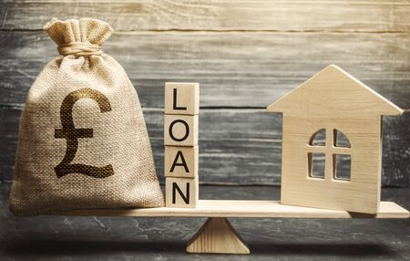 Miniature house and money bag with the word Loan on the scales. The concept of mortgage housing and real estate loans. Buy an apartment on credit. Leasing. Affordable Housing for young families. Stok Fotoğraf