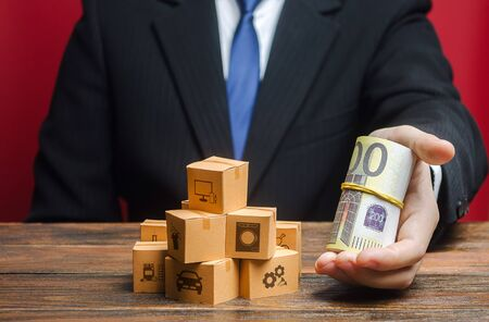 A businessman holds out a bundle of euros near a pile of boxes. Superprofits. Investments financing in production, taxes, income revenues. Trade and exchange goods, offers for cooperation. Profit