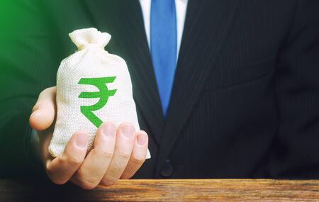 Man holds out a indian rupee money bag. Provision of money on credit, grant. Project financing. Payment purchases, profits dividends. Donations. Financial social assistance. Business investment