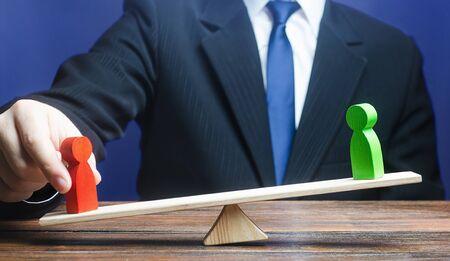 Mann stellt grüne Figur dem roten Gegner auf der Waage gegenüber. Geben Sie einen Vorteil, ändern Sie die Machtverhältnisse, ändern Sie das Ergebnis der Konfrontation. Unsichtbare helfende Hand. Unterstützen Sie den Feindgewinn, Intrigen politischen Kampf