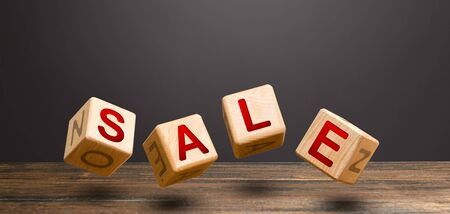 Wooden blocks form word Sale. Sales announcement and high discounts on goods. Shopping event. Promotions attracting customers attention. Marketing and targeting, advertising campaign. Sales boost