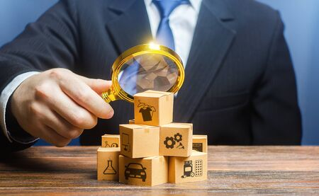 A businessman examines boxes goods with magnifying glass. Market structure research, find unoccupied target consumer niches, demand assessment. Marketing sales promotion strategy. Retailer