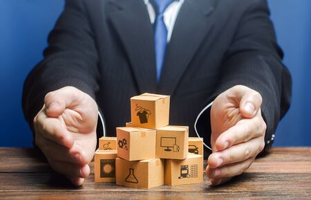Businessman covers boxes goods. Business management. Commodity circulation import export. Marketing sales, distribution. Support manufacturer, attracting investments, promoting products to new markets Stock Photo