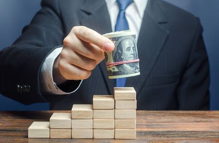Businessman puts a dollars bundle on top of stairs. Raising bids, increase interest rate deposit account growth. Salary growth and career ladder progression. Business success, company profitability.