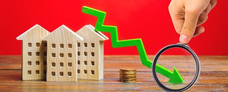 Miniature wooden houses and a green arrow down. The concept of low cost real estate. Lower mortgage interest rates. Falling prices for rental housing and apartments. Reducing demand for home buying