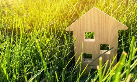 Miniature wooden house on green grass. Real estate concept. Modern housing. Eco-friendly and energy efficient house. Buying a home outside the city. Nature. Fresh air. Mortgage, loan.